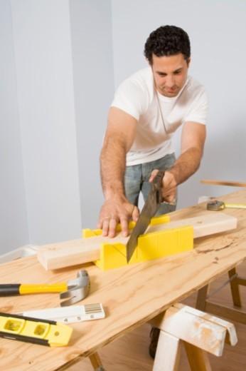 Man sawing wood : Stock Photo
