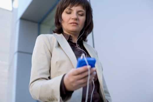 Woman listening to mp3 player : Stock Photo