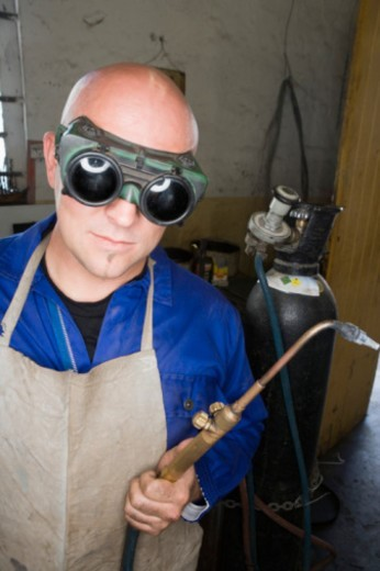 Welder with torch and goggles : Stock Photo