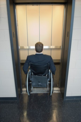Man in wheelchair entering elevator : Stock Photo