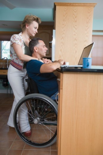 Stock Photo: 1557R-339791 Man in wheelchair with woman and laptop