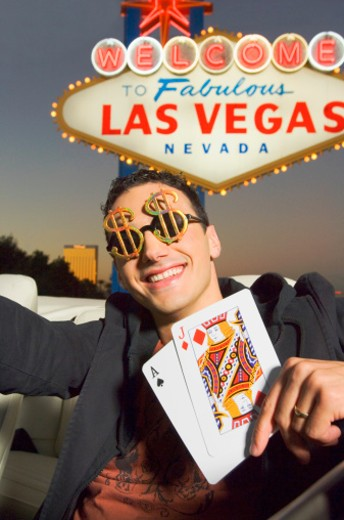 High roller holding playing cards by Las Vegas sign : Stock Photo
