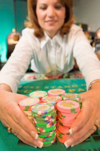 Dealer holding chips at gambling table : Stock Photo
