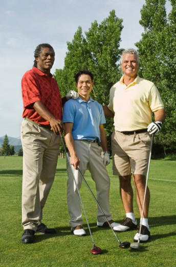 Smiling golfing friends on golf green : Stock Photo