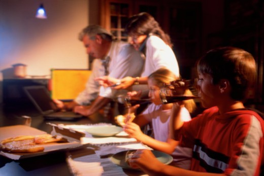 Children eating while parents work : Stock Photo