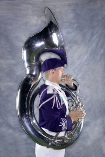 Side view of a marching band member blowing into his tuba. : Stock Photo