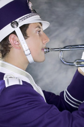 Stock Photo: 1557R-349472 Close-up profile of a band member playing the trumpet.