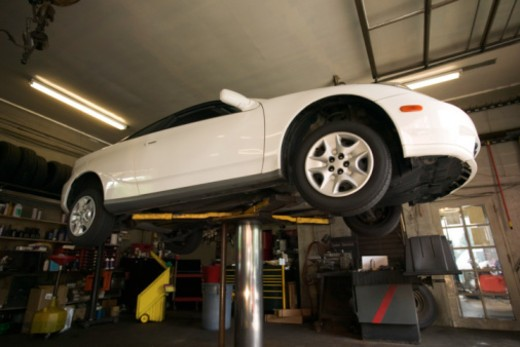 Car on lift at auto mechanic shop : Stock Photo