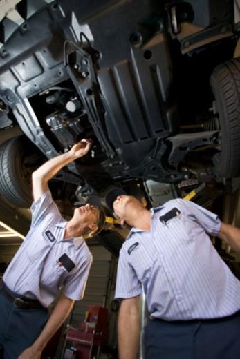 Stock Photo: 1557R-350299 Mechanics under car on lift