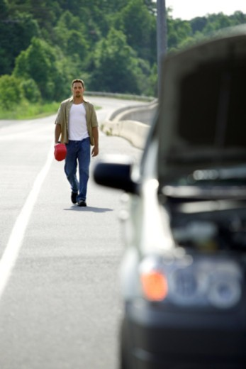 Stock Photo: 1557R-350487 Man carrying gas can back to car