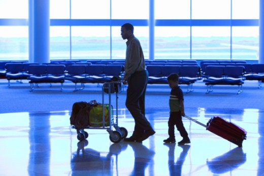 Silhouette of father and son walking through airport : Stock Photo