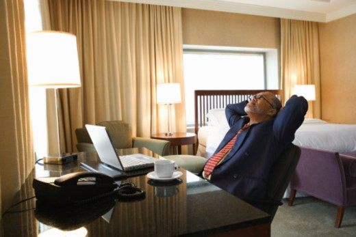 Businessman sitting in hotel room : Stock Photo