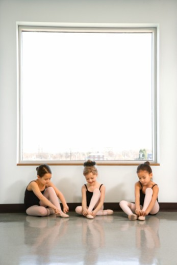 Stock Photo: 1557R-351823 Ballet students sitting by window adjusting slippers