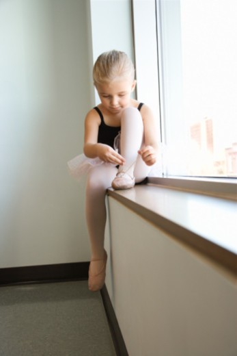 Stock Photo: 1557R-351867 Girl sitting in window adjusting ballet slippers