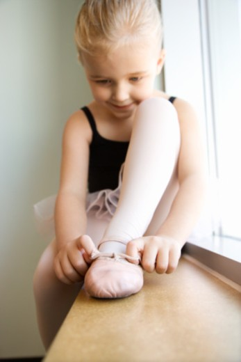 Girl sitting in window adjusting ballet slippers : Stock Photo