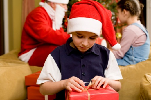 Boy opening Christmas present : Stock Photo