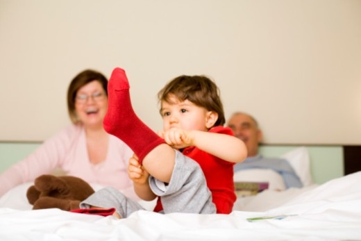 Child sitting on bed putting sock on : Stock Photo