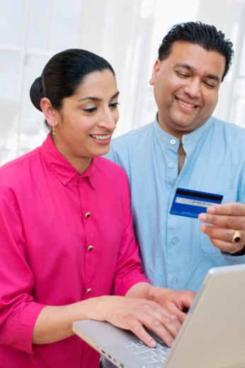 Woman and man with laptop and credit card : Stock Photo