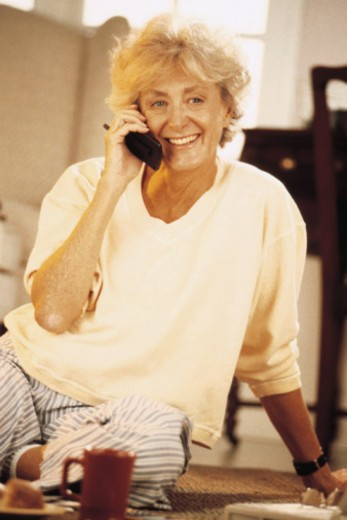 Woman sitting on floor and talking on telephone : Stock Photo