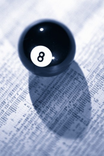 Eight ball on top of financial page of newspaper : Stock Photo
