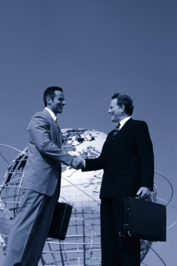 Low angle view of businessmen shaking hands outdoors : Stock Photo