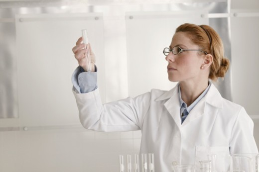Scientist looking at test tube : Stock Photo