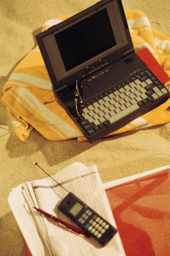 Laptop computer with cell phone and newspaper at the beach : Stock Photo