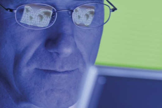 Stock Photo: 1557R-354059 Reflections of world map in eyeglasses of man at computer