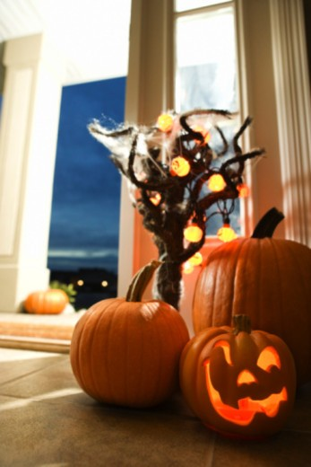 Jack-o-lantern near doorway of house : Stock Photo