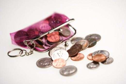 Coin purse spilling coins : Stock Photo