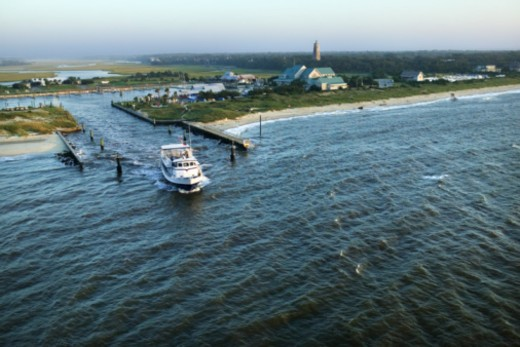 Stock Photo: 1557R-354936 Aerial view of boat leaving marina, Bald Head Island, North Carolina