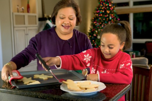Stock Photo: 1557R-355338 A girl and her grandmother bake Christmas cookies in the kitchen.