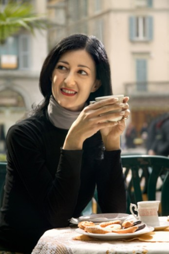 Stock Photo: 1557R-355558 A woman looks to her right, smiling while holding a cup of tea in a cafe.