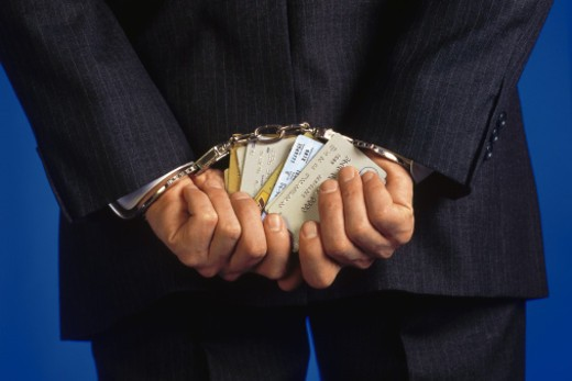 Handcuffed businessman holding credit cards : Stock Photo