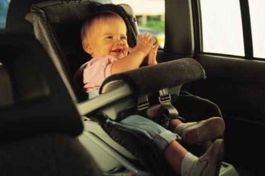 Stock Photo: 1557R-357578 Baby sitting in a car seat and clapping hands