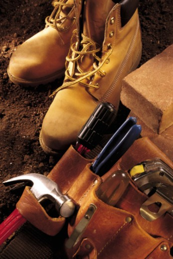 Stock Photo: 1557R-358179 Construction boots with tool belt and bricks