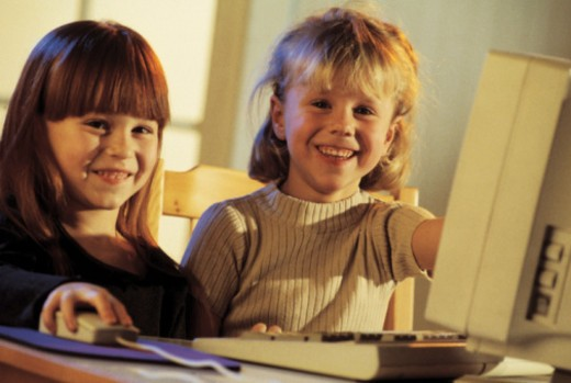 Children smiling and using computer : Stock Photo
