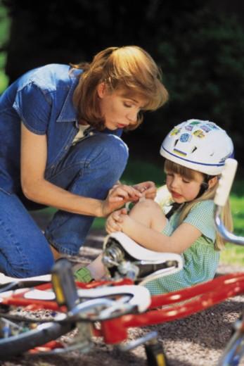Mother bandaging daughter's knee injury : Stock Photo