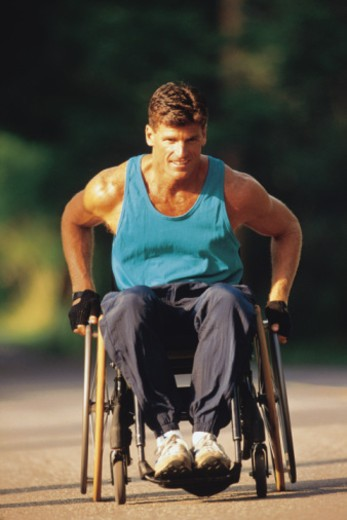 Athletic man pushing himself in wheelchair : Stock Photo