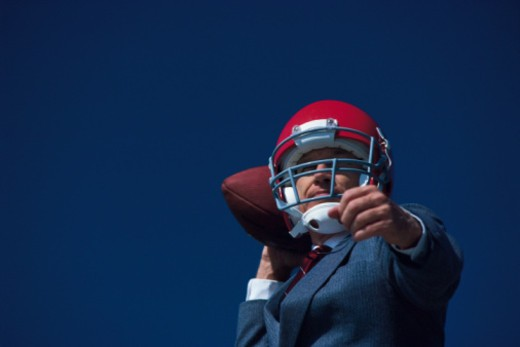 Businessman posing in football helmet with ball : Stock Photo