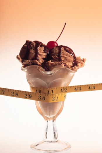 Ice cream sundae with measuring tape around it : Stock Photo