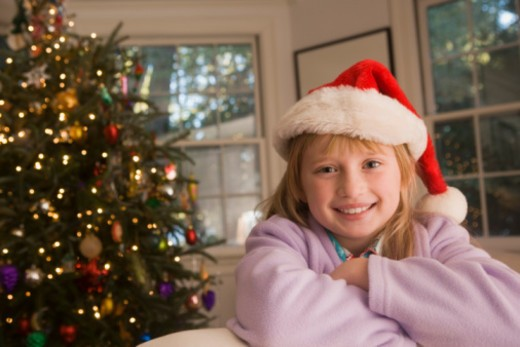 Girl in Santa Claus hat by Christmas tree : Stock Photo