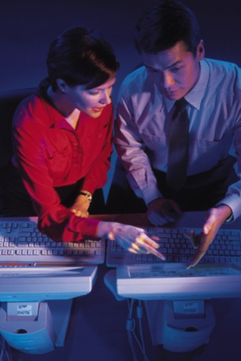 Man and woman working in front of computers : Stock Photo