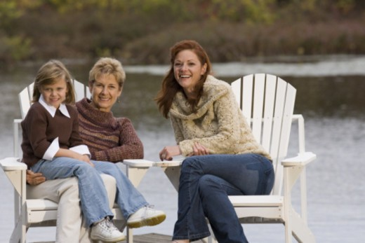 Stock Photo: 1557R-364229 Three generations of women sitting by lake