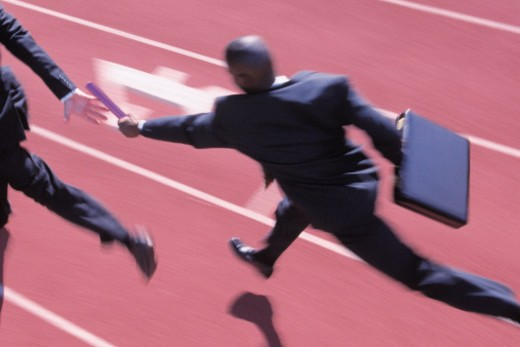 Stock Photo: 1557R-364313 Businessmen running on track and handing off baton