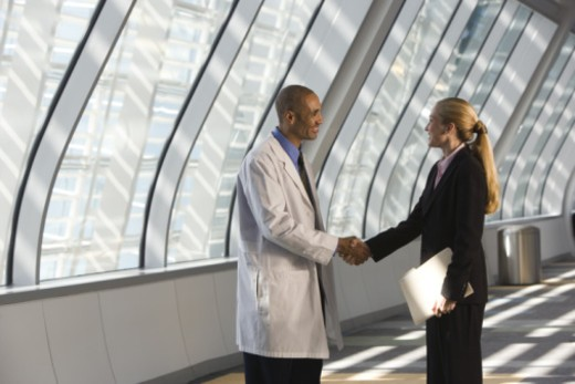 Stock Photo: 1557R-364481 Doctor and businesswoman shaking hands