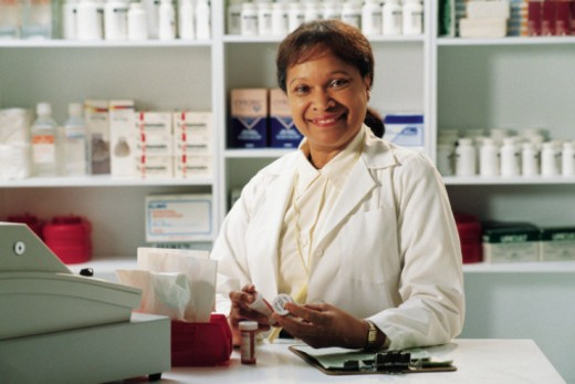 Pharmacist behind counter : Stock Photo