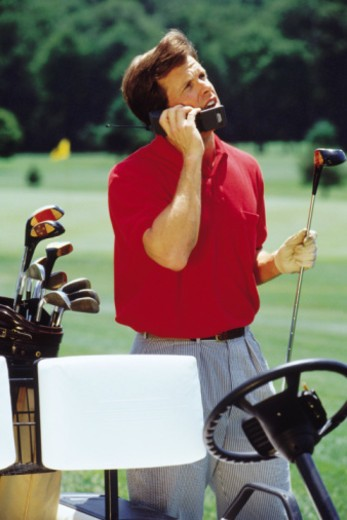 Man on cell phone while on golf course : Stock Photo