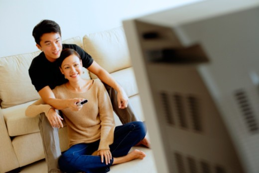 Man and woman watching TV together : Stock Photo