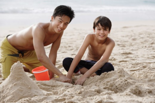 Father and son building sand castle together : Stock Photo